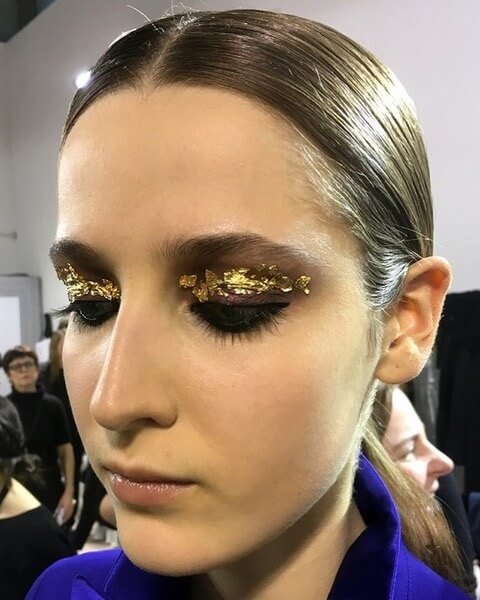 Makeup artist Diane Kendal adds an artistic touch to Akris' beauty look with abstract gold leaf.